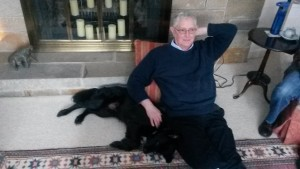 dog sitting on the floor with a man